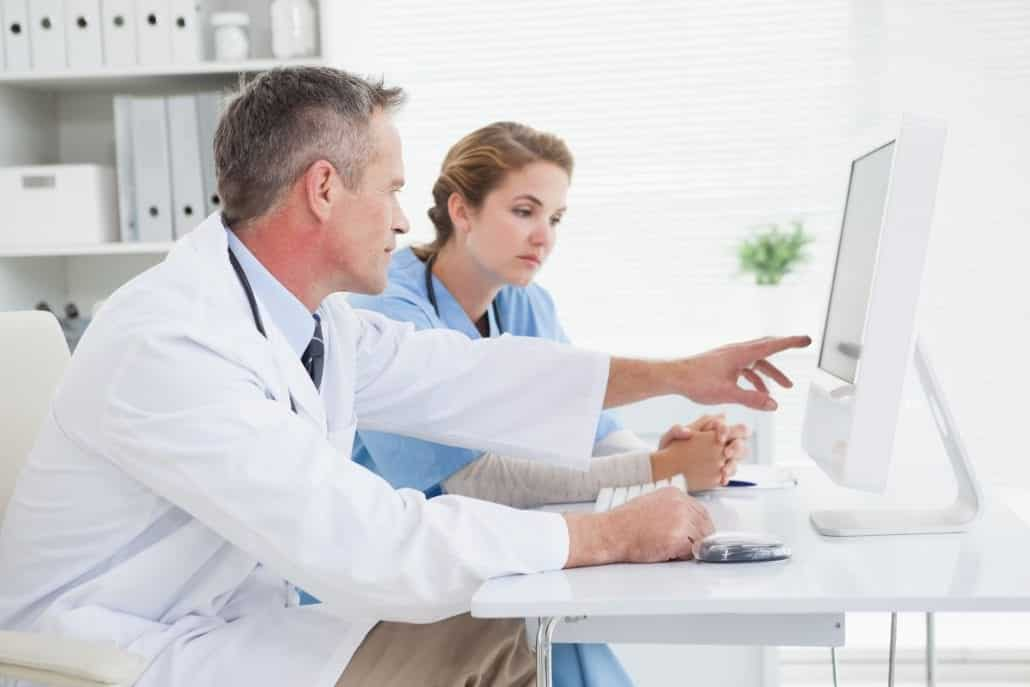 Physician sitting with nurse pointing to patient medical record on computer screen